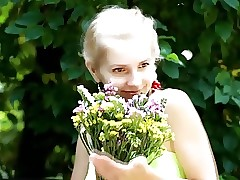beautiful fresh blonde girl likes flowers